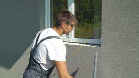 Man worker in safety glasses and protective gloves measuring external sill and PVC window frame size. Male worker in safety glasses and protective gloves stock footage
