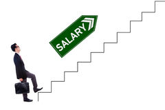 Male worker with salary text on stairs. Photo of a young businessman walking upwards on the stairs with salary text on the signpost Royalty Free Stock Photos