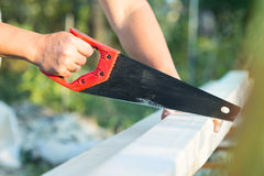 Male worker sawing a board. Hacksaws Royalty Free Stock Photo