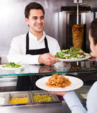 Male worker serving customer. Happy adult male serving customer with smile at shawarma place Royalty Free Stock Image