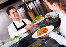 Male worker serving customer. Happy male serving customer with smile at shawarma place Stock Photos