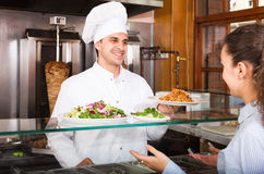 Male worker serving customer. Happy male worker serving customer with smile at shawarma place Stock Image