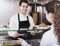 Male worker serving customer. Positive male worker serving customer with smile at shawarma place Stock Image