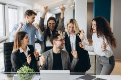 Male worker share good news with multiracial colleagues in shared workplace, diverse employees scream with happiness excited with stock photography