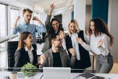 Male worker share good news with multiracial colleagues in shared workplace, diverse employees scream with happiness excited with royalty free stock photo