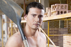 Male worker with shovel and bricks Royalty Free Stock Image