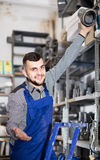Male worker showing his workplace at workshop. Young smiling russian male worker showing his workplace at workshop Stock Image