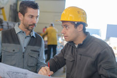 Male worker showing something to co-worker at notebook papers. Male worker showing something to co-worker at his notebook papers Royalty Free Stock Photo