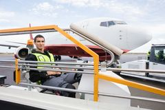 Male Worker Sitting On Luggage Conveyor Truck. Portrait of male worker sitting on luggage conveyor truck against airplane at airport Stock Photography