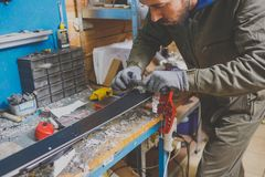 A male worker in a ski service workshop repairs the sliding surface of the skis. Close-up of a hand with a plastic scrapper for re. Moving wax, removing new wax Stock Photography