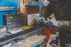A male worker in a ski service workshop repairs the sliding surface of the skis. Close-up of a hand with a plastic scrapper for re. Moving wax, removing new wax Stock Photo
