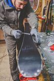 A male worker in a ski service workshop repairs the sliding surface of the skis. Close-up of a hand with a plastic scrapper for re. Moving wax, removing new wax Stock Image