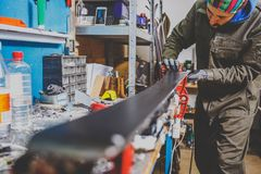 A male worker in a ski service workshop repairs the sliding surface of the skis. Close-up of a hand with a plastic scrapper for re. Moving wax, removing new wax Royalty Free Stock Photos