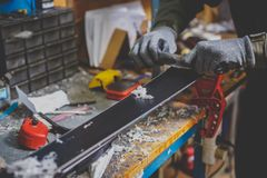 A male worker in a ski service workshop repairs the sliding surface of the skis. Close-up of a hand with a plastic scrapper for re stock photos