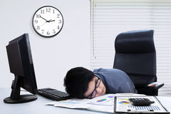 Male worker sleeping on the table in office Stock Image