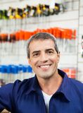 Male Worker Smiling In Hardware Shop. Portrait of mature male worker smiling in hardware shop Royalty Free Stock Images