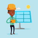 Male worker of solar power plant. Engineer working on digital tablet at solar power plant. African-american worker of solar power plant. Engineer in hard hat Royalty Free Stock Image