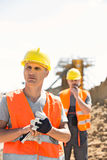 Male worker standing at construction site with colleague in background Royalty Free Stock Image