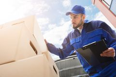 Male Worker Standing Near Cardboard Box Holding Clipboard. Low Section Of Young Male Worker Standing Near Cardboard Box Holding Clipboard Stock Images