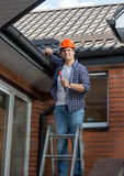 Male worker standing on step ladder in front of house. Young male worker standing on step ladder in front of house Stock Images