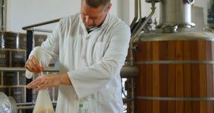 Male worker stirring liquor in flask 4k stock footage