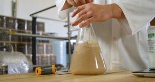 Male worker stirring liquor in flask 4k stock video