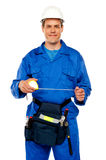 Male worker stretching measuring tape. Isolated against white background Royalty Free Stock Images