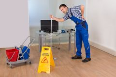 Male worker suffering from back pain. Male Janitor Suffering From Back Pain While Mopping In Office Stock Image