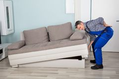 Worker Suffered From Back Pain While Lifting Sofa. Male Worker Suffering From Back Pain While Lifting Sofa In Living Room At Home Stock Photos