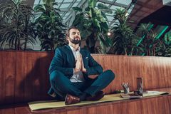 Male worker meditating on bench in office. Royalty Free Stock Photos