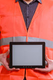 Male worker with tablet. Technological development in company. Part body man worker in orange uniform safety vest with tablet. Repairman inspector at work Stock Images