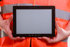 Male worker with tablet. Technological development in company. Part body man worker in orange uniform safety vest with tablet. Repairman inspector at work Stock Image