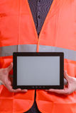 Male worker with tablet. Technological development in company. Part body man worker in orange uniform safety vest with tablet. Repairman inspector at work Stock Photos