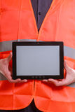 Male worker with tablet. Technological development in company. Part body man worker in orange uniform safety vest with tablet. Repairman inspector at work Royalty Free Stock Photos