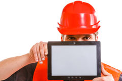 Male worker with tablet. Technological development in company. Young handsome man worker in safety vest and hard hat with tablet. Repairman inspector at work Royalty Free Stock Photography