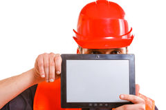 Male worker with tablet. Technological development in company. Young handsome man worker in safety vest and hard hat with tablet. Repairman inspector at work Royalty Free Stock Images