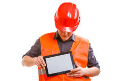 Male worker with tablet. Technological development in company. Young handsome man worker in safety vest and hard hat with tablet. Repairman inspector at work Stock Photography