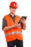 Male worker with tablet. Technological development in company. Young handsome man worker in safety vest and hard hat with tablet. Repairman inspector at work Royalty Free Stock Photos