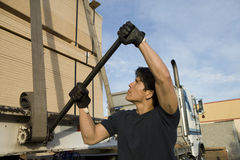 Male Worker Tightening Belt Of A Trailer With Metal Rod Royalty Free Stock Images