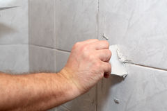 Male worker tiling a wall. The male hand with the rubber stick applies grout on a seam between tiles in a bathroom. Home repairs Stock Images