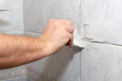 Male worker tiling a wall. The male hand with the rubber stick applies grout on a seam between tiles in a bathroom. Home repairs Royalty Free Stock Photography