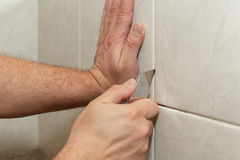 Male worker tiling a wall. Male hands with knife removing the old grout. Replacing old grout between tiles. Raking out tiles for regrouting Royalty Free Stock Image