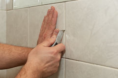 Male worker tiling a wall. Male hands with knife removing the old grout. Replacing old grout between tiles. Raking out tiles for regrouting Stock Photography