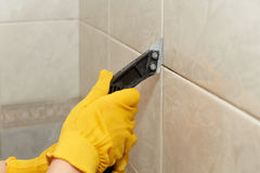 Male worker tiling a wall. Male hands with knife removing the old grout. Replacing old grout between tiles. Raking out tiles for regrouting Stock Photos
