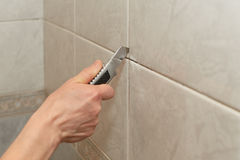 Male worker tiling a wall. Male hands with knife removing the old grout. Replacing old grout between tiles. Raking out tiles for regrouting Stock Image