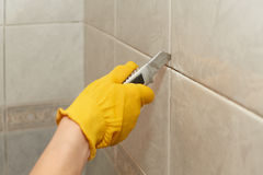 Male worker tiling a wall. Male hands with knife removing the old grout. Replacing old grout between tiles. Raking out tiles for regrouting Royalty Free Stock Images