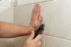 Male worker tiling a wall. Male hands with knife removing the old grout. Replacing old grout between tiles. Raking out tiles for regrouting Stock Images