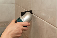 Male worker tiling a wall. Male hands with renovator multi-tool removing the old grout. Replacing old grout between tiles. Raking out tiles for regrouting Stock Photo