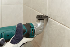 Male worker tiling a wall. Male hands with renovator multi-tool removing the old grout. Replacing old grout between tiles. Raking out tiles for regrouting Royalty Free Stock Photos