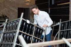 Male worker transporting bottles of wine to storage. At sparkling wine factory Stock Photo